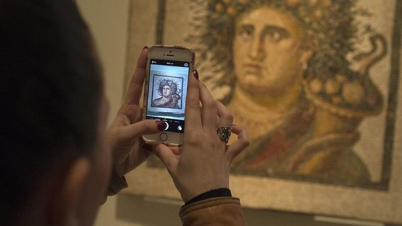"""A woman takes a picture with her cell phone of """"Genius of the Year"""", a mosaic dating from the late 2nd century, at the National Archaeological Museum in Madrid March 27, 2014. REUTERS/Juan Medina (SPAIN - Tags: SOCIETY) - RTR3IV4A"""